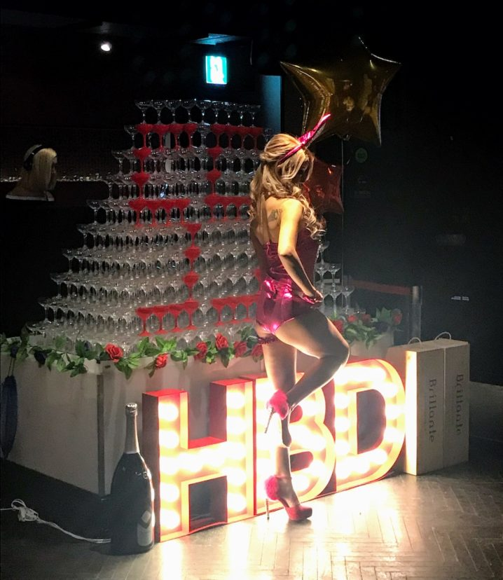 「55」の数字の入ったシャンパンタワーの前で、バニーガールがポージング.巨大なシャンパンボトルも配備.